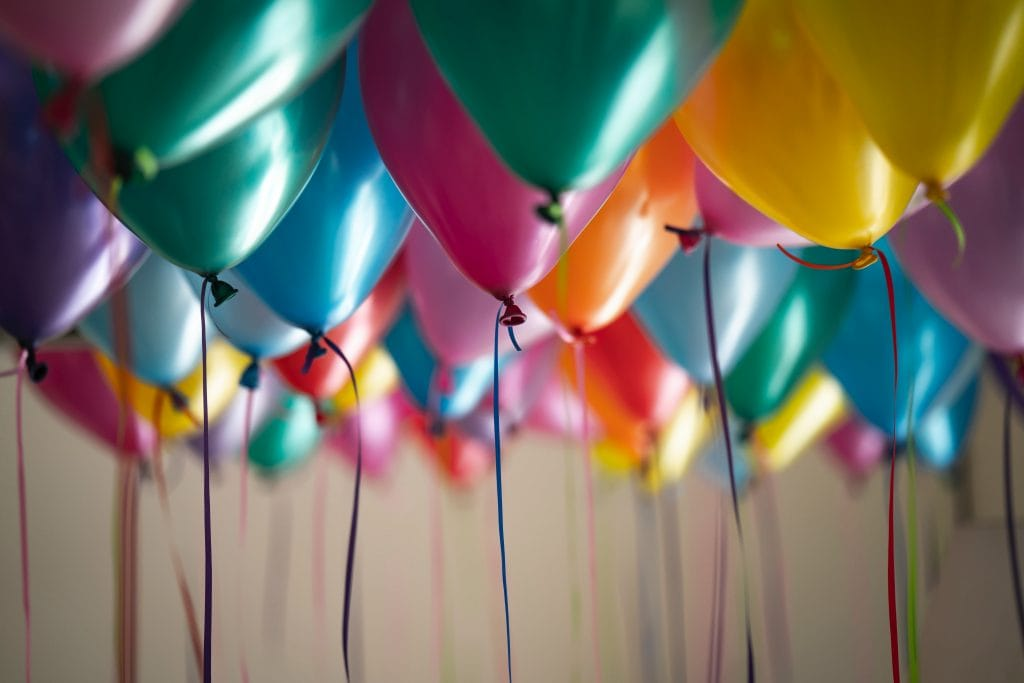 a bunch of colourful helium balloons on the ceiling