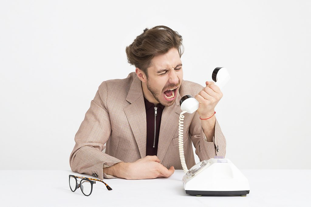 frustrated boss shouting into the phone